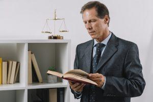 A imagem contém um juiz de Direito lendo um livro sobre leis.