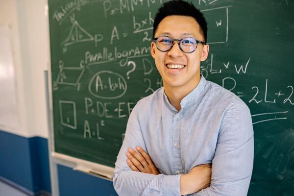 A imagem contém um jovem sorrindo após resolver problemas, no quadro ao fundo, usando macetes para resolver questões de raciocínio lógico.
