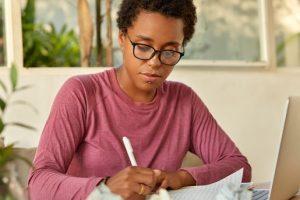 A imagem contém uma jovem usando macetes para resolver questões de raciocínio lógico.