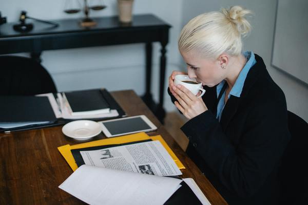 A imagem contém uma defensora pública em seu local de trabalho após ser aprovada em um concurso público para Direito.