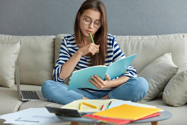 A imagem contém uma jovem estudante segurando um livro aberto com uma mão e apoiando uma caneta na boca. A jovem busca como se preparar para OAB.
