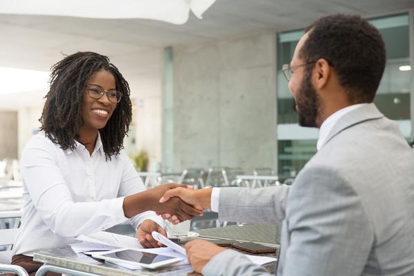 A imagem contém uma cliente sendo atendida por um bacharel em Direito quanto a um contrato. Eles trocam um aperto de mão e estão sorridentes.