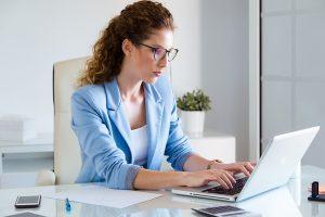 A imagem contém uma jovem advogada, que tem interesse em seguir carreira jurídica,preparando-se para um concurso público.