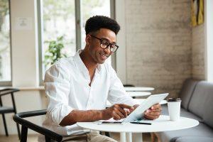 A imagem contém um jovem profissional em Direito Digital sentado em uma mesa com seu tablet na mão. Ele está sorrindo enquanto olha e mexe em seu tablet.