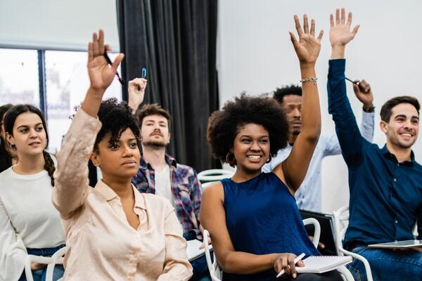 A imagem apresenta uma sala de aula com seis alunos. Todos eles estão com as mãos levantadas para participar da aula. Saber por que fazer Direito torna a dinâmica das aulas muito mais interessante.