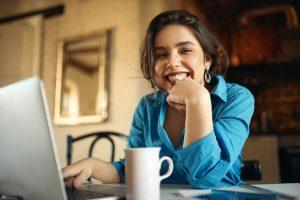 A imagem contém uma estagiária sorrindo e comemorando o Dia do Estagiário.