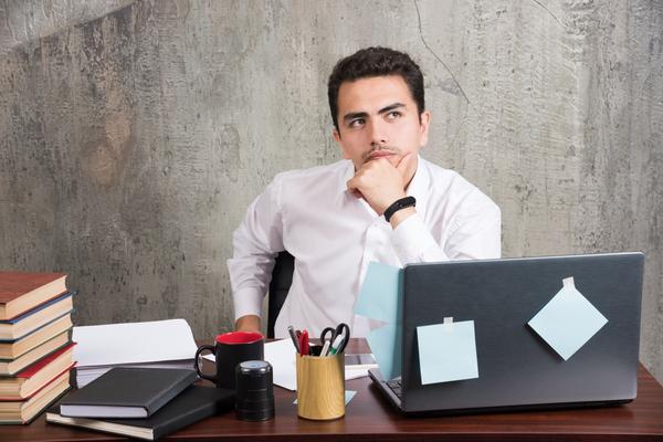 A imagem contém um jovem em seu escritório com a mão apoiada no queixo e a expressão de dúvida sobre qual o melhor Vade Mecum para OAB.