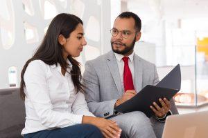 A imagem contém um defensor público atendendo uma cliente. Os dois estão sentados lado a lado e o defensor público mostra o conteúdo de uma pasta para sua cliente.