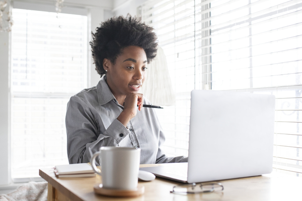 A imagem contém uma jovem advogada em exercício, aplicando a relação entre Direito e tecnologia ao participar de uma audiência online.