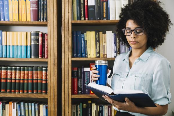 """A imagem contém uma jovem em uma biblioteca segurando e olhando para um Vade Mecum. Após se perguntar """"Qual o melhor Vade Mecum para OAB?"""", a jovem escolheu o ideal."""