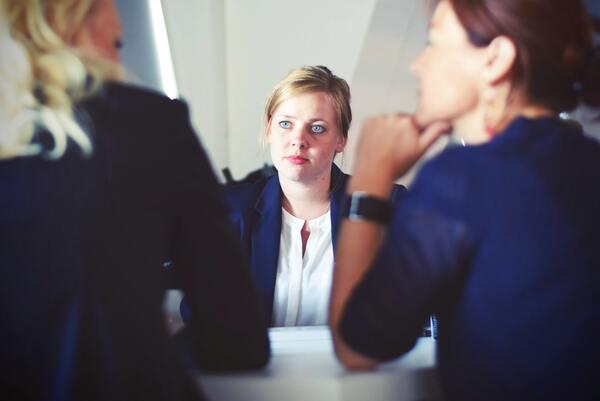 A imagem contém uma advogada falando com seus clientes sobre o direito de ficar calado.