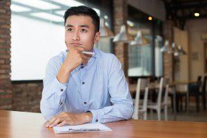 A imagem contém um jovem com uma prancheta. Sua mão segura uma caneta ao mesmo tempo que apoia seu queixo. Revelando uma expressão de dúvida sobre como montar um cronograma de estudos OAB.