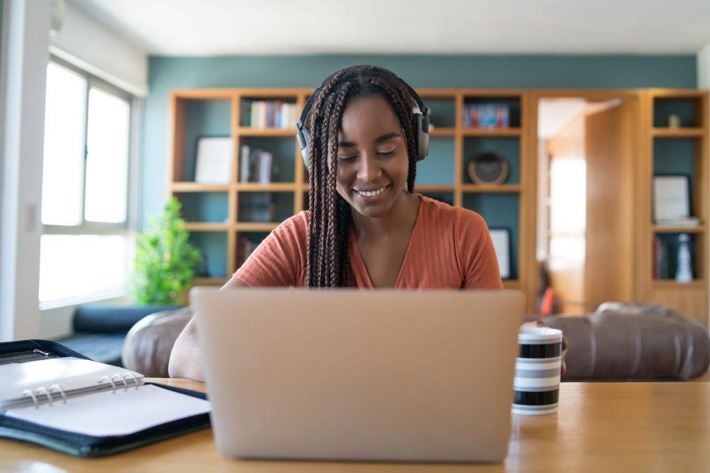 A imagem contém uma jovem em seu computador montando seu cronograma de estudos OAB