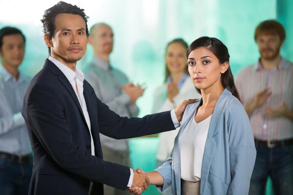 A imagem contém um advogado do Direito Trabalhista dando um aperto de mão e apoiando o ombro de sua cliente. Ao fundo os colegas de trabalho batem palmas.