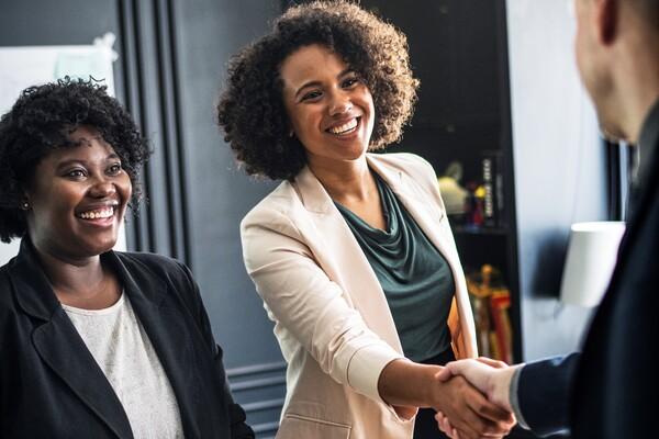 A imagem contém uma advogada do Direito Trabalhista dando um aperto de mão em seu cliente. Ela está acompanhada de sua assistente.
